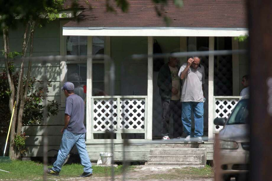 A group of men walk outside the home where high-risk sex offenders had been moved to on the 9300 block of W. Montgomery Road in the Acres Homes neighborhood Friday, April 4, 2014, in Houston. 