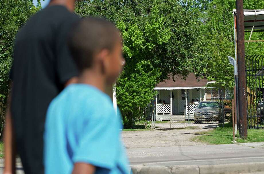 A 17-year-old and his 7-year-old brother walk past the home where high-risk sex offenders had been moved to on the 9300 block of W. Montgomery Road in the Acres Homes neighborhood Friday, April 4, 2014. Photo: Johnny Hanson, Houston Chronicle / © 2014  Houston Chronicle