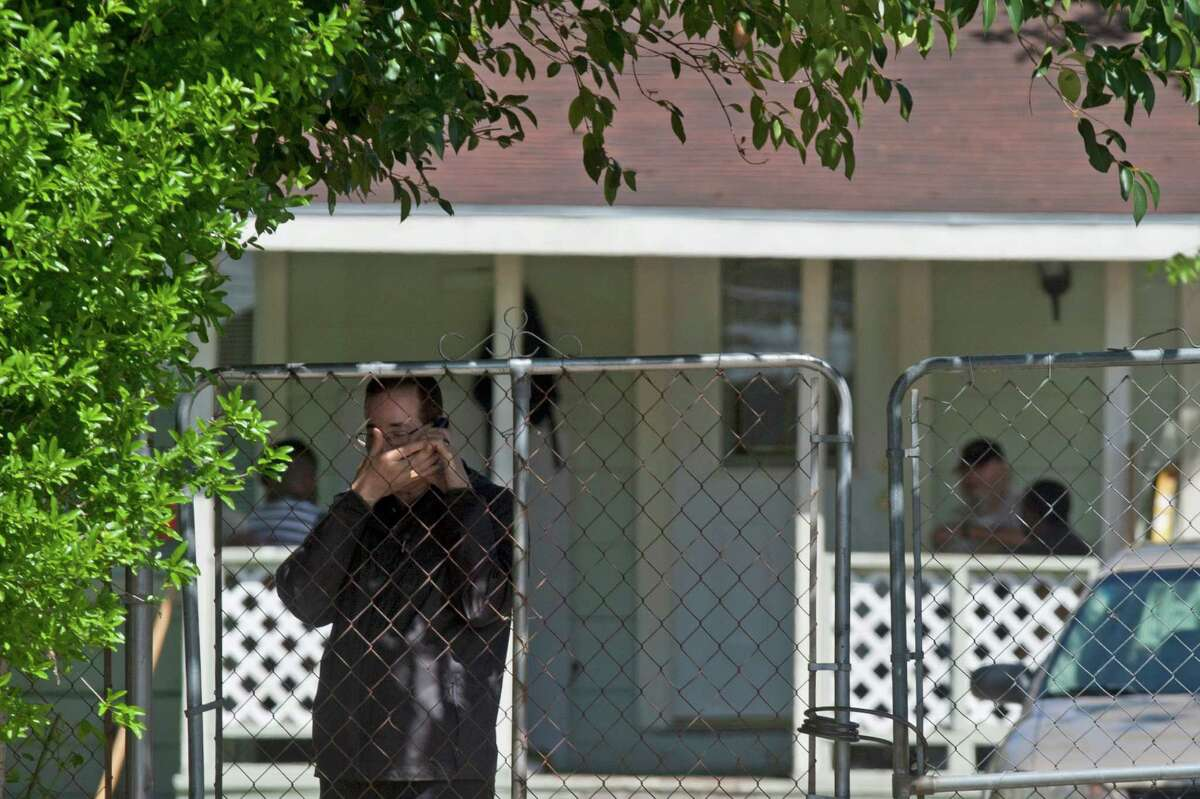 A man covers his face while talking on the phone outside the home where high-risk sex offenders had been moved to on the 9300 block of W. Montgomery Road in the Acres Homes neighborhood Friday, April 4, 2014, in Houston. The high-risk offenders had been moved out of the halfway house because they were taking up beds there that were needed for low-risk regular felons who were exiting prison on parole, for treatment and rehabilitation programs.