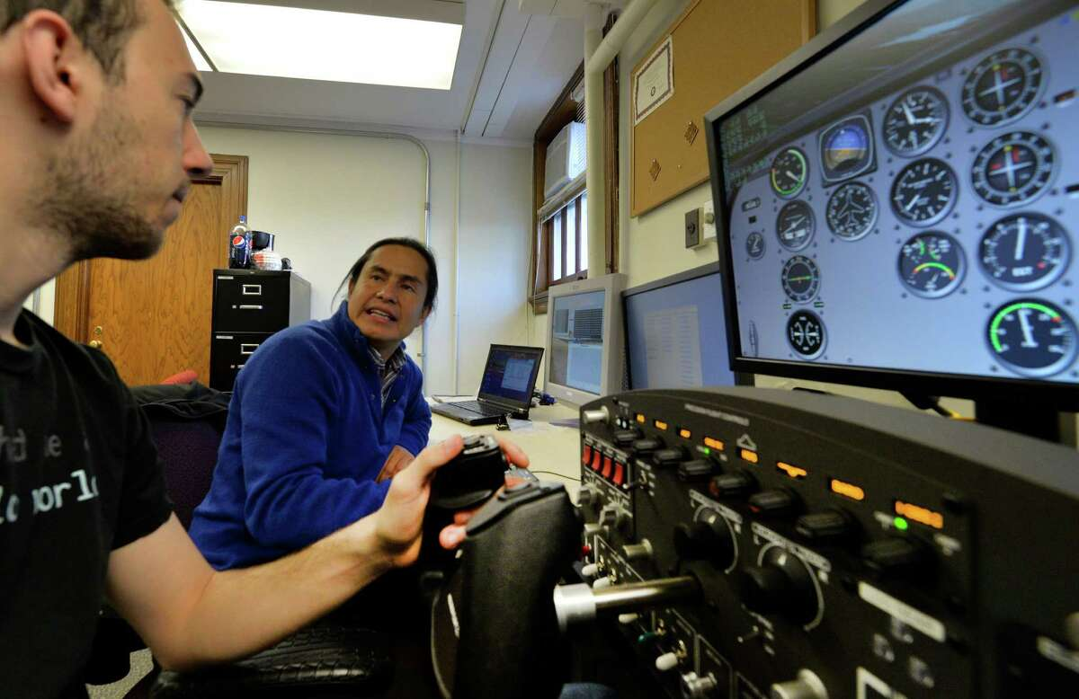 Rensselaer Polytechnic Institute professor Carlos Varela,right, with the help of student Alessandro Galli demonstrates autopilot software that Varela developed Thursday, April 3, 2014, at RPI in Troy, N.Y. (Skip Dickstein / Times Union)