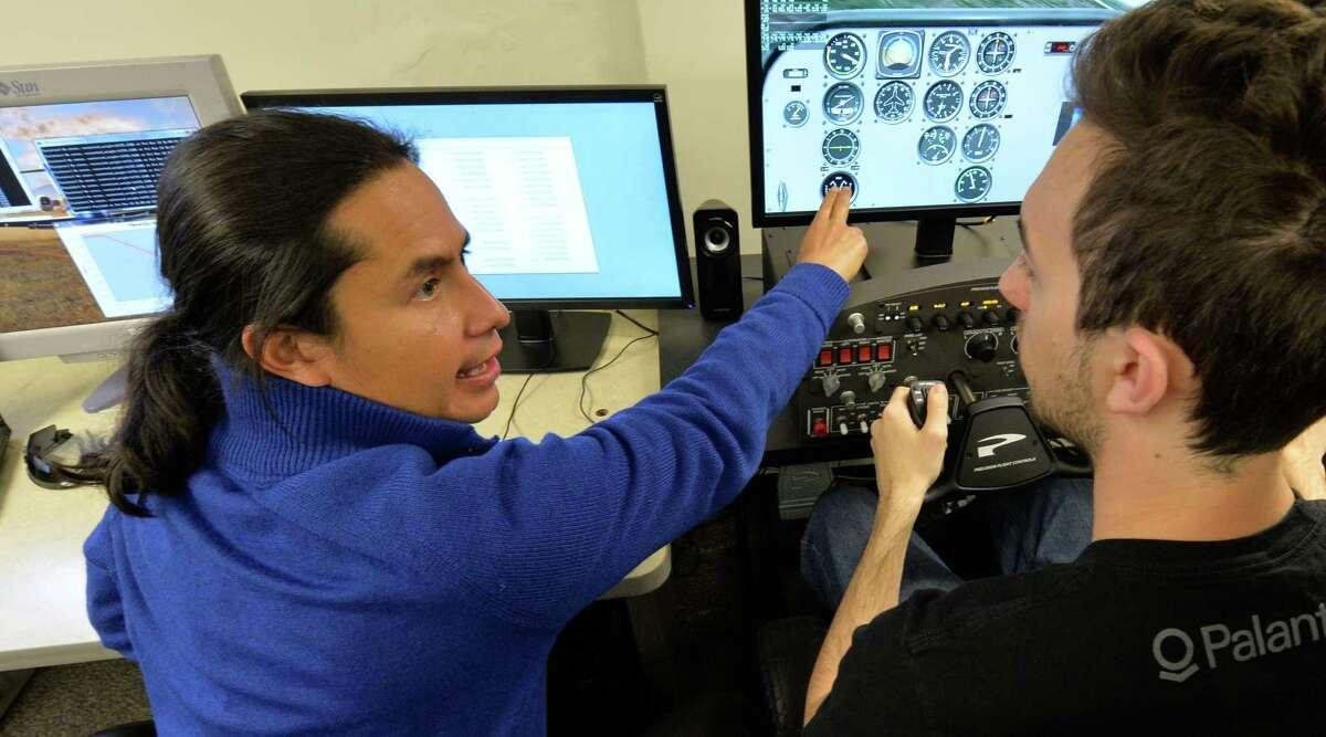Rensselaer Polytechnic Institute professor Carlos Varela, left, with the help of student Alessandro Galli demonstrates autopilot software that Varela developed Thursday, April 3, 2014, at RPI in Troy, N.Y. (Skip Dickstein / Times Union)