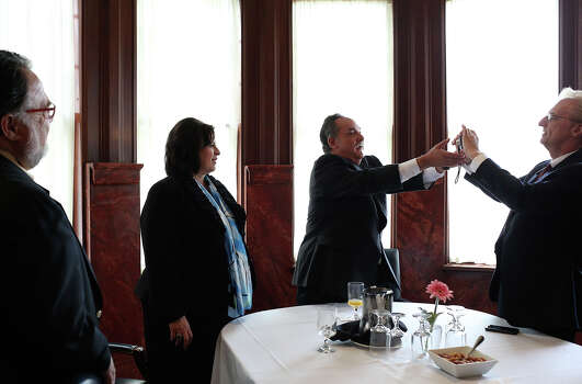 Sol Villasana, center, adjusts his camera so David Griggs, right, can photograph him with State Senator Leticia Van de Putte at the conclusion of a roundtable discussion with small business owners at the Belo Mansion in Dallas as she campaigns for Lt. Governor on Thursday, April 3, 2014. Photo: Lisa Krantz, SAN ANTONIO EXPRESS-NEWS / SAN ANTONIO EXPRESS-NEWS