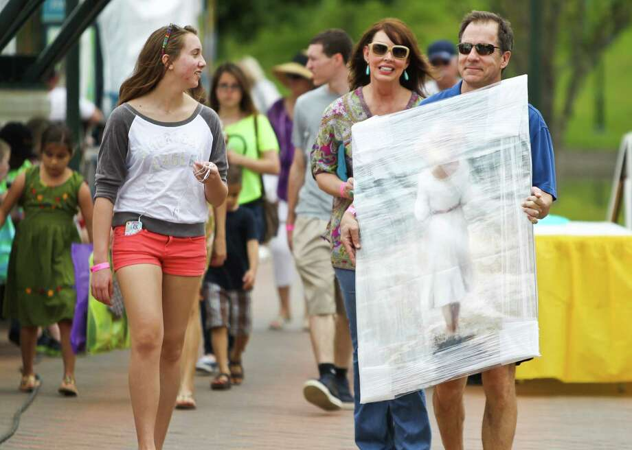 What will America look like in 2060? Pew Research Center attempted to answer that question, and here is what the researchers found.Pictured: Robin Robinson, right, carries a heavy piece of original artwork made by Steven Graber during The Woodlands Waterway Arts Festival, Sunday, April 14, 2013. Photo: Nick De La Torre, Staff / © 2013 Houston Chronicle