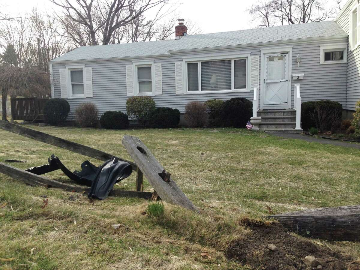 A mangled bumper lies amid pieces of a wrecked fence at a residence in Riverside. Police say a drunken man caused mayhem at the address Thursday, believing he was at the home of an ex-girlfriend ... who lives in Milford.
