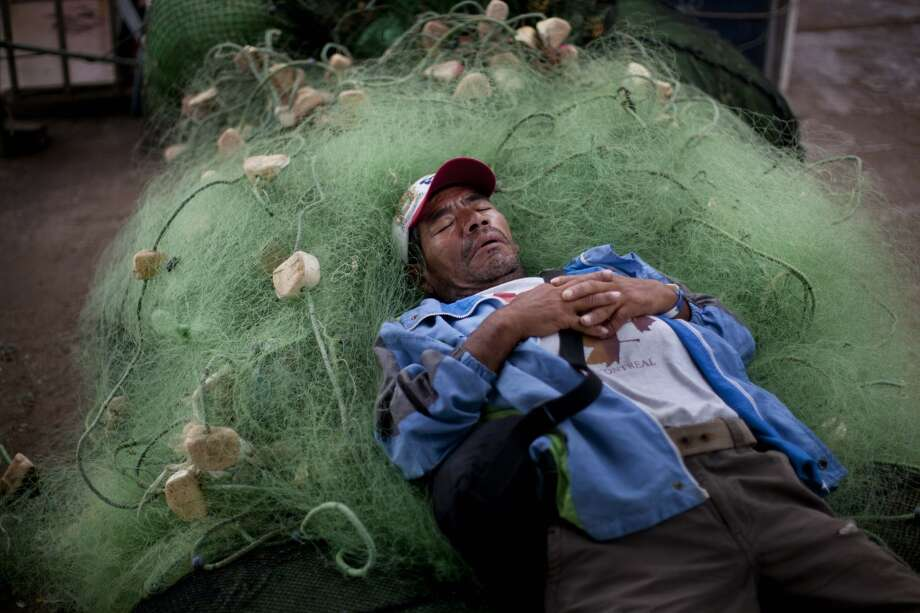Peru: A small scale fisherman naps on a jumble of fishing nets in Lima, Peru. Photo: Rodrigo Abd, Associated Press