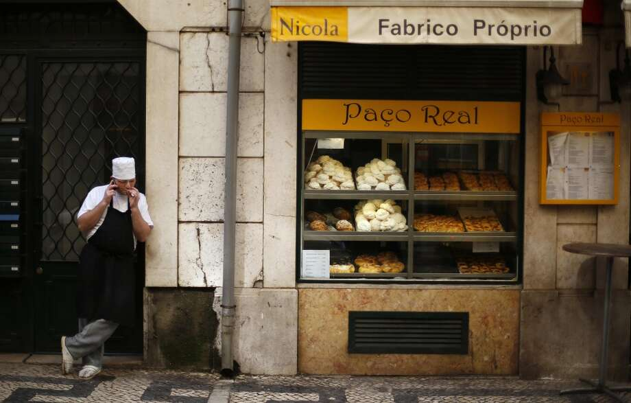 Portugal: A pastry chef smokes as he talks on the phone in downtown Lisbon. Photo: RAFAEL MARCHANTE, Reuters