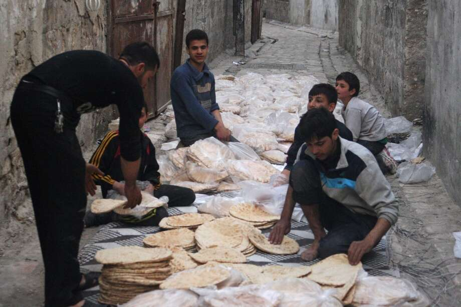 Syria: Men arrange bread along a street in Old Aleppo. Photo: Photo, Reuters