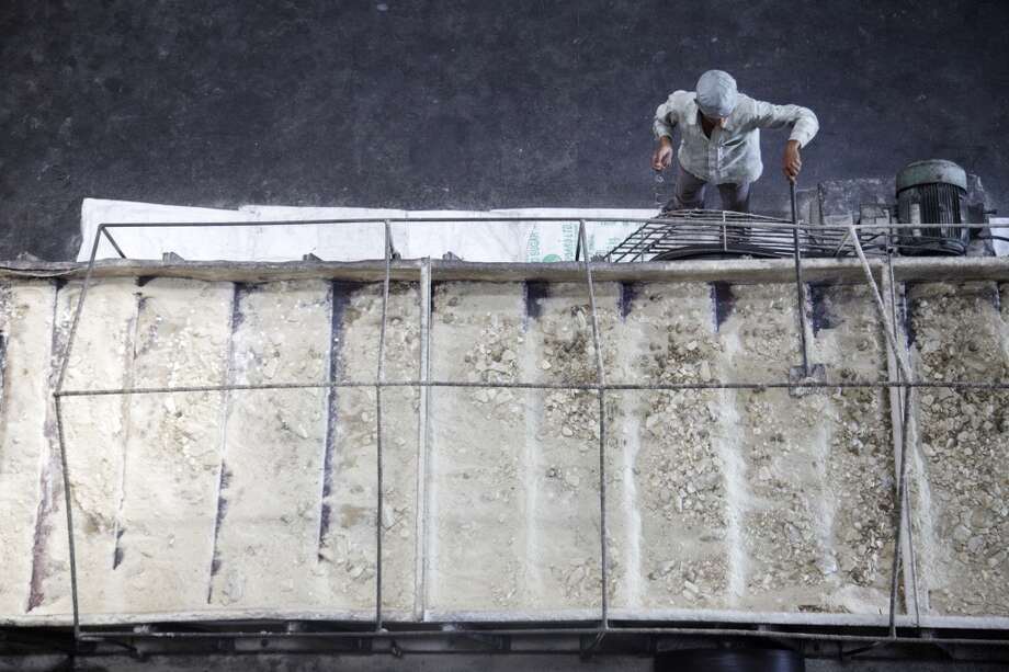 India: A worker checks raw sugar on a conveyor at the Simbhaoli Sugars Ltd. manufacturing plant in Simbhaoli, Uttar Pradesh, India. Photo: Kuni Takahashi, Bloomberg