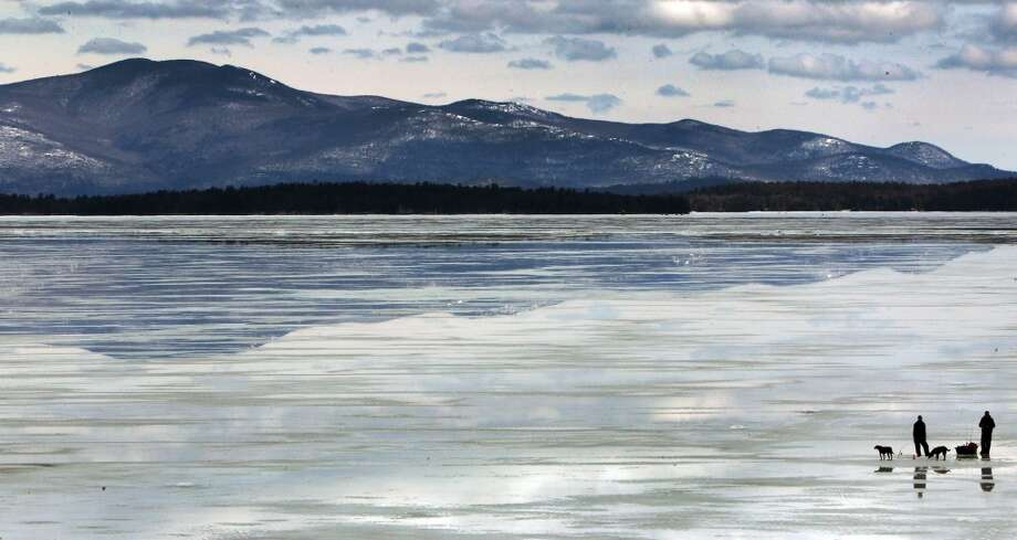 New Hampshire:  Ice fisherman stand on a frozen part of Lake Winnipesaukee in Gilford, N.H. on Saturday March 29, 2014. The April 1 opening day of salmon season will offer little open water for fisherman. Parts of the lake are still 2 to 3 feet thick of ice. Photo: Jim Cole, Associated Press