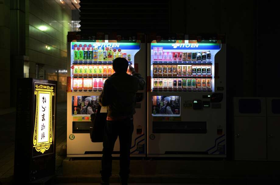 Japan: A man purchases a soft drink from an Ito En Ltd. vending machine at night in Tokyo, Japan. Photo: Noriko Hayashi, Bloomberg