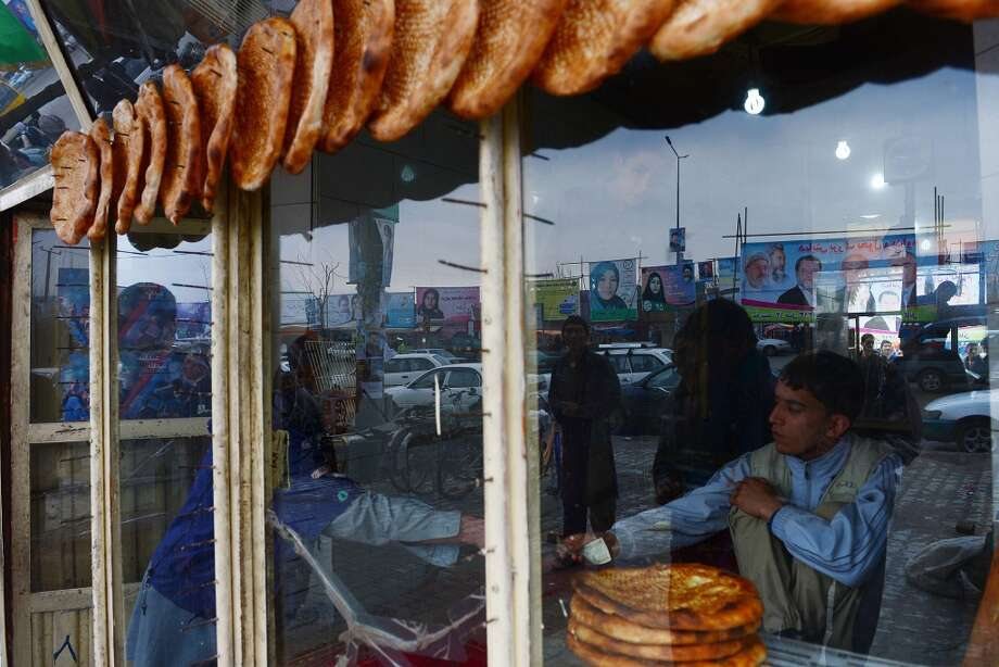 Afghanistan: An Afghan shop attendant sells bread in a store as political billboards are reflected in the window in Kabul on April 4, 2014. Some 12 million Afghans will go to the polls on April 5 to elect a new President. Photo: WAKIL KOHSAR, AFP/Getty Images