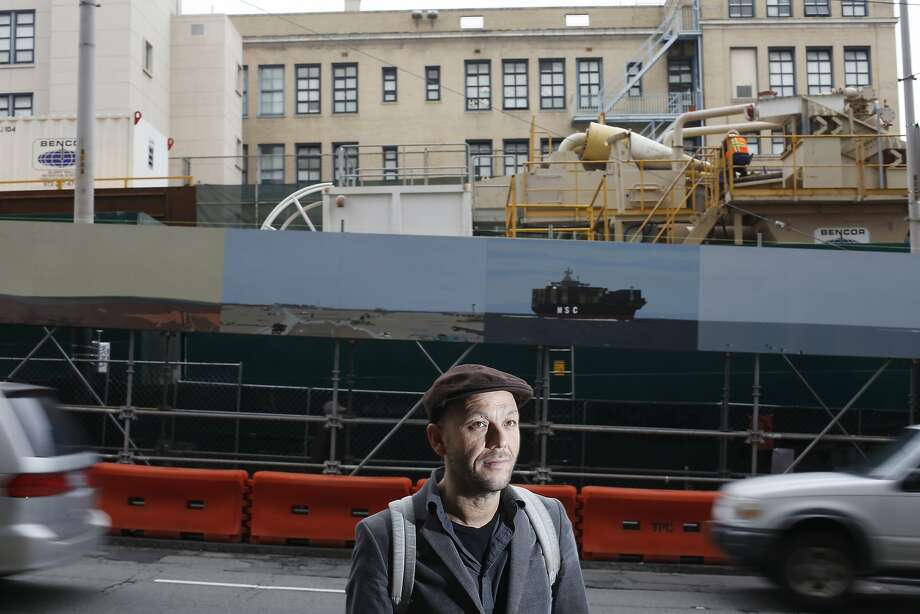 Kota Ezawa stands in front of his 150-foot mural where Muni is excavating for the Central Subway in Chinatown. Photo: Mike Kepka, The Chronicle