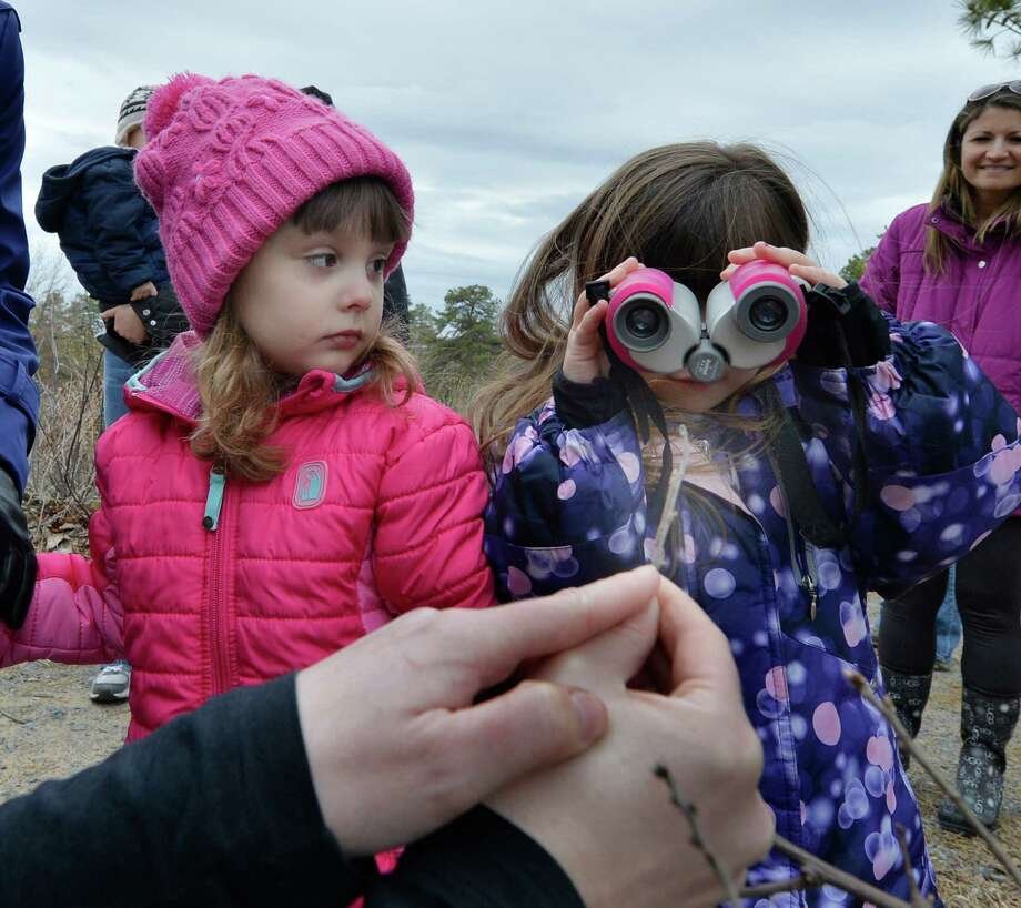 Environmental educator Amanda Dillon identifies butterfly eggs as Emiliana Ilagan, 4 and Mia Paglialonga, 4, watch during the Signs of Spring hike April 4, 2014 at the Discovery Center at the Albany Pine Bush Preserve in Albany, N.Y.   (Skip Dickstein / Times Union) Photo: Skip Dickstein / 00026375A