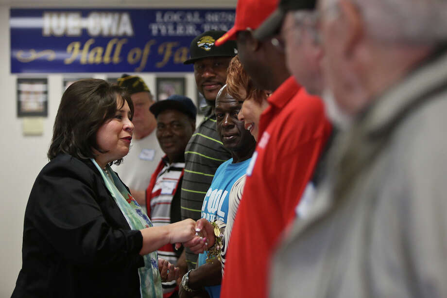 State Senator Leticia Van de Putte hands challenge coins to veterans after she called them to the front of the room to be honored during a campaign event in Tyler on Friday, April 4, 2014. As the Chair of the Veteran Affairs and Military Installations Senate Committee, the Senator gives the coins in appreciation of veterans' service. Photo: Lisa Krantz, SAN ANTONIO EXPRESS-NEWS / SAN ANTONIO EXPRESS-NEWS