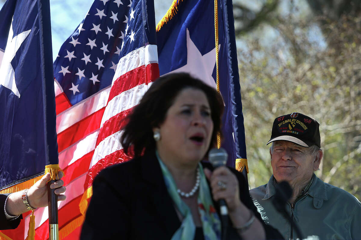 Ralph Sanders holds a flag after high winds knocked one over as State Senator Leticia Van de Putte speaks during a Meet and Greet at Festival Park as she campaigns for Lt. Governor in Nacogdoches Friday, April 4, 2014.