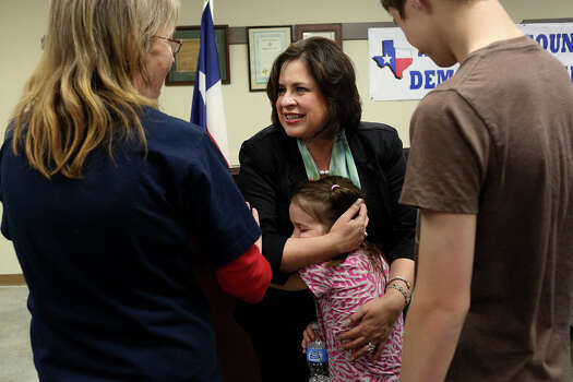 State Senator Leticia Van de Putte embraces Hope Beatty, 8, as she talks with Hope's grandmother, Debra Tullos, left, and her grandson, Halstin Beatty, 14, as she campaigns for Lt. Governor at the Labor Temple in Lufkin on Friday, April 4, 2014. Photo: Lisa Krantz, SAN ANTONIO EXPRESS-NEWS / SAN ANTONIO EXPRESS-NEWS