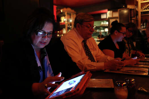 State Senator Leticia Van de Putte, sitting with her husband, Pete Van de Putte, looks at the weather radar to ensure her campaign bus will avoid the storm that spurned two tornados near Dallas at pizzaLOUNGE in Dallas after a day filled with campaign events on Thursday, April 3, 2014. The campaign waited for the storm to pass before driving to Tyler for an early morning Meet and Greet. Photo: Lisa Krantz, SAN ANTONIO EXPRESS-NEWS / SAN ANTONIO EXPRESS-NEWS