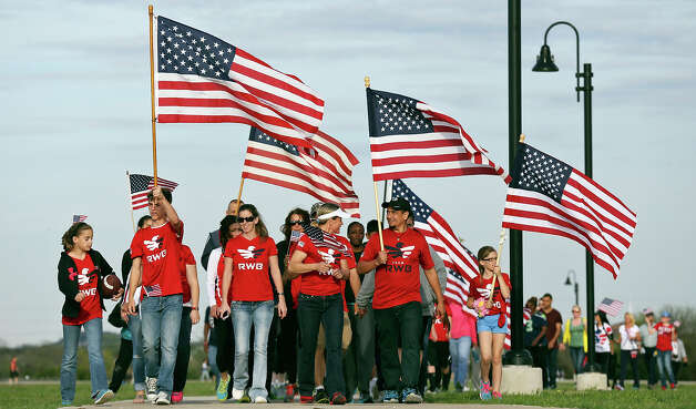 People take part in a flag walk around Lions Club Park in tribute to the Fort Hood shooting victims Friday April 4, 2014 in Killeen, Texas. Photo: Edward A. Ornelas, San Antonio Express-News / ©2014 San Antonio Express-News
