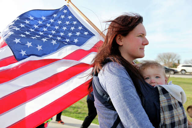 Melissa Phillips carries her daughter Sierra, 1, while taking part in a flag walk around Lions Club Park in tribute to the Fort Hood shooting victims Friday April 4, 2014 in Killeen, Texas. Photo: Edward A. Ornelas, San Antonio Express-News / ©2014 San Antonio Express-News