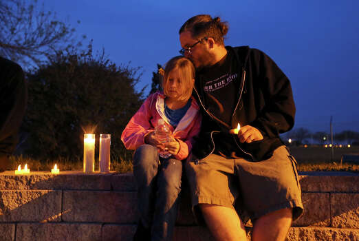Lily Muncy, 9, (left) and her father Malachi Muncy take part in a candle light vigil for the Fort Hood shooting victims at the east gate Friday April 4, 2014 in Killeen, Texas. Photo: Edward A. Ornelas, San Antonio Express-News / ©2014 San Antonio Express-News