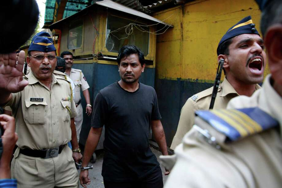 One of the four men convicted in the gang-rape of a photojournalist in August is escorted outside a prison in Mumbai. Three of the four men were also involved in the rape of a call center worker. Photo: Rafiq Maqbool, STF / AP