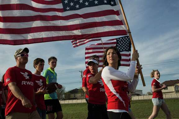 Members of the military, veterans and civilians march in Killeen to pay tribute to the slain Fort Hood victims Friday.