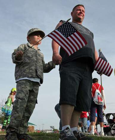 U.S. Army Spc. Mark Power and his son Damon, 6, wait for the start of a flag walk around Lions Club Park in tribute to the Fort Hood shooting victims Friday April 4, 2014 in Killeen, Texas. Photo: Edward A. Ornelas, San Antonio Express-News / ©2014 San Antonio Express-News