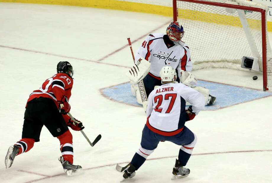 New Jersey Devils center Ryan Carter, left, scores a goal on Washington Capitals goalie Jaroslav Halak, top, of Slovakia, as defenseman Karl Alzner (27) watches during the third period of an NHL hockey game, Friday, April 4, 2014, in Newark, N.J. The Devils won 2-1. (AP Photo/Julio Cortez) ORG XMIT: NJJC109 Photo: Julio Cortez / AP