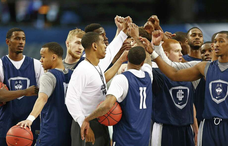 Connecticut coach Kevin Ollie and his team huddle as they prepare for their NCAA Final Four game against Florida at AT&T Stadium in Arlington. Photo: Ron Jenkins / Fort Worth Star-Telegram