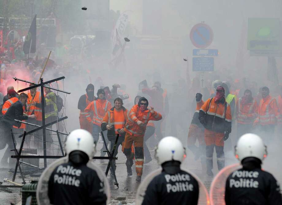 Protesters throw stones at police Friday at the end of a labor demonstration in Brussels. Photo: JOHN THYS, Stringer / AFP