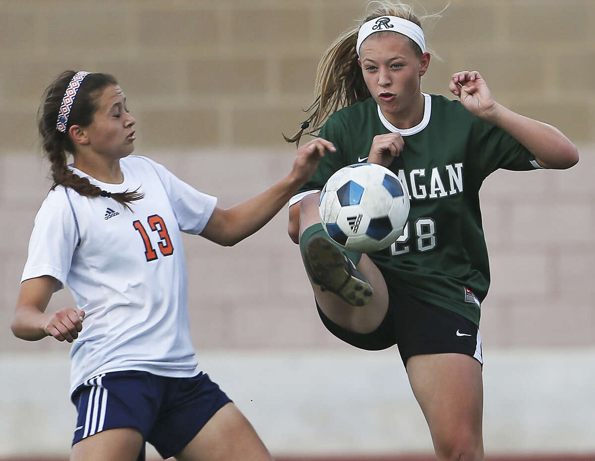 Reagan's Taylor Olson keeps the ball away from Brandeis' Kelsey Kohler during the Rattlers' easy victory in a Class 5A playoff match at Farris Stadium. Olson scored in the triumph.