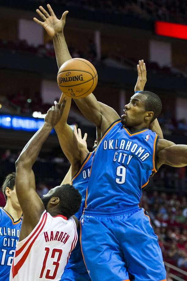 Thunder forward Serge Ibaka knocks away a shot by Rockets guard James Harden. Photo: Smiley N. Pool, Houston Chronicle