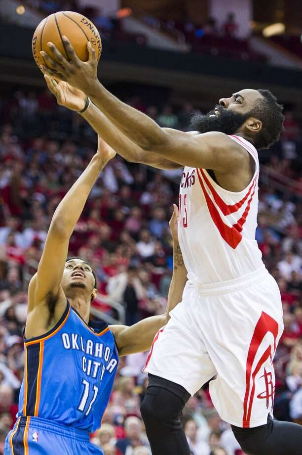 Rockets guard James Harden drives to the basket against Thunder guard Jeremy Lamb. Photo: Smiley N. Pool, Houston Chronicle