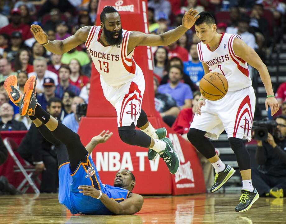 Rockets guard James Harden leaps over Thunder forward Kevin Durant (35) while chasing a loose ball with guard Jeremy Lin. Photo: Smiley N. Pool, Houston Chronicle