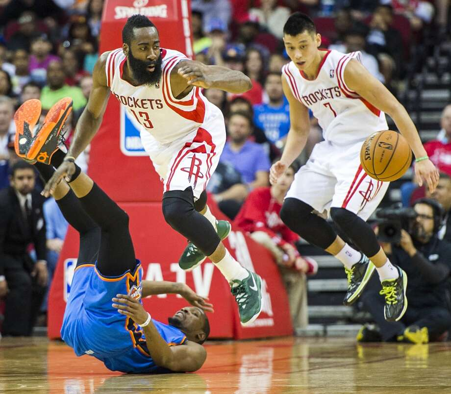 Rockets guard James Harden leaps over Thunder forward Kevin Durant while chasing a loose ball with guard Jeremy Lin. Photo: Smiley N. Pool, Houston Chronicle