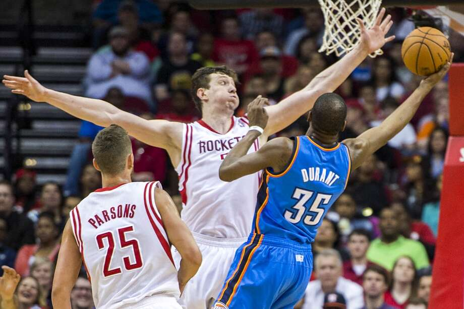 Rockets center Omer Asik defends a shot by Thunder forward Kevin Durant. Photo: Smiley N. Pool, Houston Chronicle