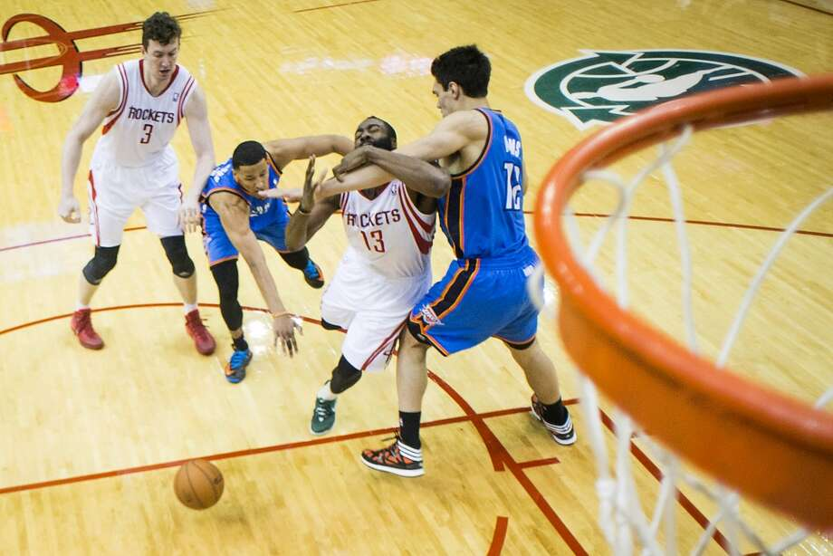Rockets guard James Harden is fouled by Thunder center Steven Adams. Photo: Smiley N. Pool, Houston Chronicle