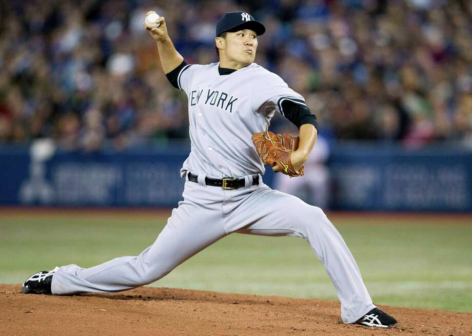 New York Yankees starting pitcher Masahiro Tanaka makes his major league debut as he pitches against the Toronto Blue Jays during first inning AL baseball action in Toronto on Friday, April 4, 2014. (AP Photo/The Canadian Press,Nathan Denette) ORG XMIT: NSD108 Photo: Nathan Denette / The Canadian Press