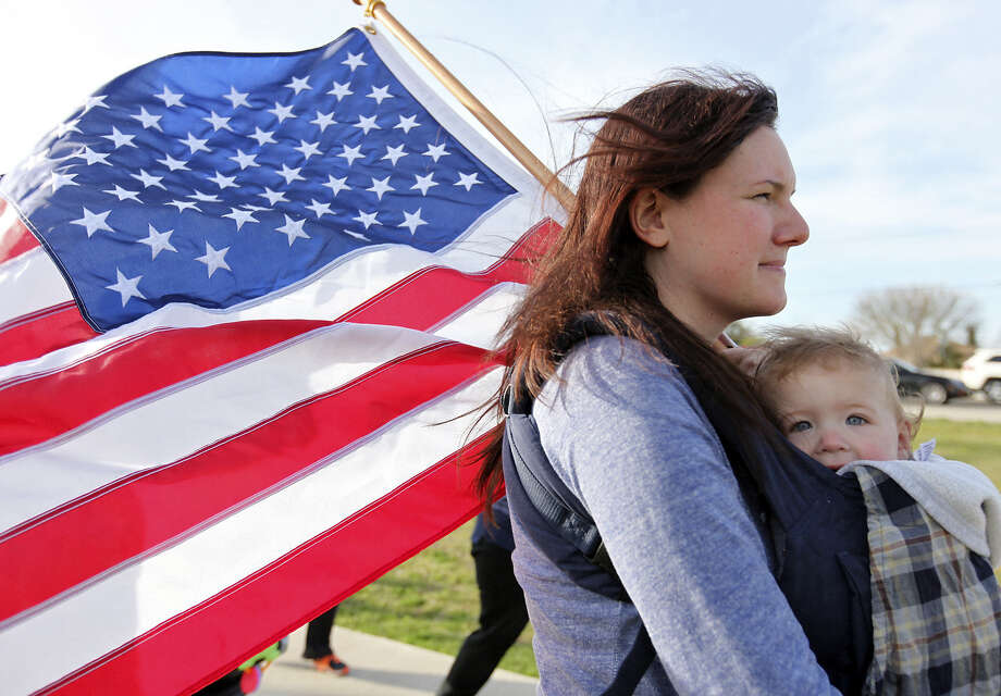 Melissa Phillips carries her daughter, Sierra, while taking part in a flag walk. / ©2014 San Antonio Express-News