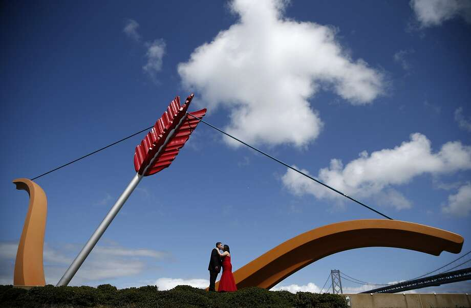 "Newlyweds Flor Perez (R) and Jose Ramirez, both 27 and from Reno, Nevada, kiss in front of ""Cupid's Span"", a sculpture by Claes Oldenburg and Coosje van Bruggen, and the Bay Bridge in San Francisco, California April 4, 2014. REUTERS/Lucy Nicholson (UNITED STATES - Tags: SOCIETY TPX IMAGES OF THE DAY) Photo: Lucy Nicholson, Reuters"