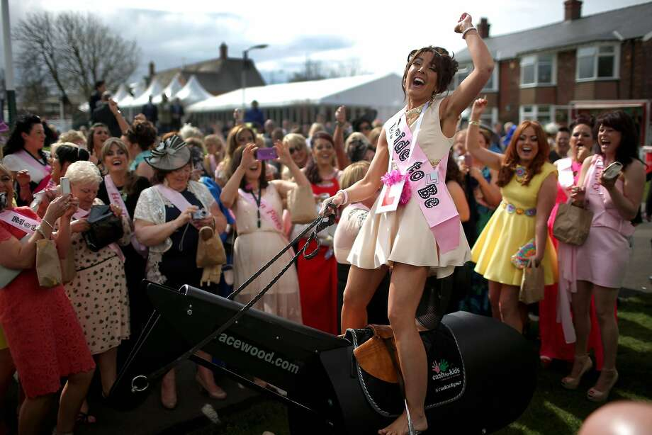 AINTREE, ENGLAND - APRIL 04:  Bride-to-be Gemma Blease enjoys a ride on a horse racing simulator as she and her hen party enjoy the atmosphere of Ladies Day at the Aintree Grand National Festival meeting on April 4, 2014 in Aintree, England. Friday is traditionally Ladies day at the three-day meeting of the world famous Grand National Festival where fashion and dressing to impress is as important as the racing.  (Photo by Christopher Furlong/Getty Images) *** BESTPIX *** Photo: Christopher Furlong, Getty Images