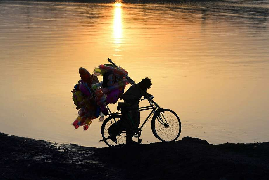 Returning home with unsold inflatables: A balloon vendor pushes his bicycle along the Ravi River in Lahore. Photo: Arif Ali, AFP/Getty Images