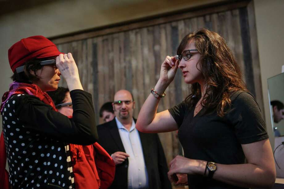 Amy-Ellen Trefsger, left, is helped by Margot Boyer-Dry as she tries on Google Glass during a public preview on Friday, April 4, 2014. The Google device will be available for the public to try on April 5th and 6th. Photo: JOSHUA TRUJILLO, SEATTLEPI.COM / SEATTLEPI.COM