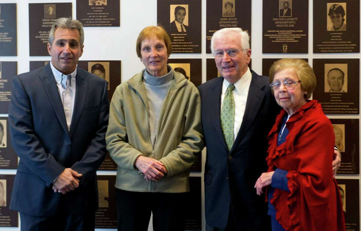 From left, Dennis Paglialunga, Betty Blake (mother of Jason Blake), Don Cook and Barbara Rioux (mother of Allyson Rioux) pose for a photo during the unveiling of plaques at the Fairfield County Sports Hall of Fame at UConn Stamford on Wednesday, April 2, 2014.