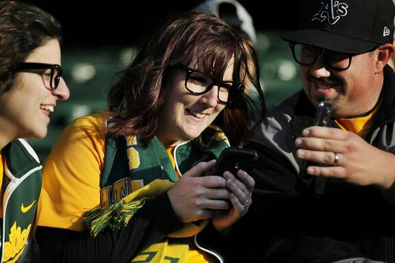 Greg Mallia, 31, right, shows his wife Megan Mallia, 29, center, his phone while she uses hers for Instagram as friend Hannah Tool 25, left, looks on before a scheduled game between the Oakland A's and the Seattle Mariners April 4, 2014 at O.co Coliseum in Oakland, Calif. The game was postponed due to field conditions following a rainy afternoon. The A's are one of 19 other MLB teams to install Apple's iBeacon technology, which allows fans to check in using the At The Ballpark app, so they can receive special in-game offers and discounts.