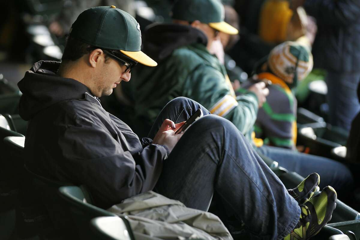 Andrew Wallace, 34, uses the Instagram app on his phone before a scheduled game between the Oakland A's and the Seattle Mariners April 4, 2014 at O.co Coliseum in Oakland, Calif. The game was postponed due to field conditions following a rainy afternoon. The A's are one of 19 other MLB teams to install Apple's iBeacon technology, which allows fans to check in using the At The Ballpark app, so they can receive special in-game offers and discounts.