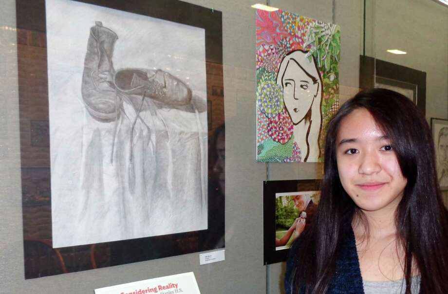 "Angela Yu, 16, a Staples High School sophomore, stands in front of the Westport Library's Riverwalk display case where her graphite on paper titled ""Old Shoes"" is included in the Emerging Artists show. Photo: Meg Barone / Westport News"