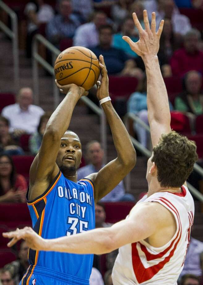 Thunder forward Kevin Durant shoots over Omer Asik for a three-pointer to give him 25 points in the game to tie Michael Jordan's  record of 40 consecutive games of scoring at least 25. Photo: Smiley N. Pool, Houston Chronicle