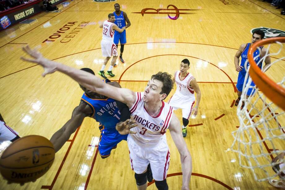 Rockets center Omer Asik defends a shot by Thunder guard Reggie Jackson. Photo: Smiley N. Pool, Houston Chronicle