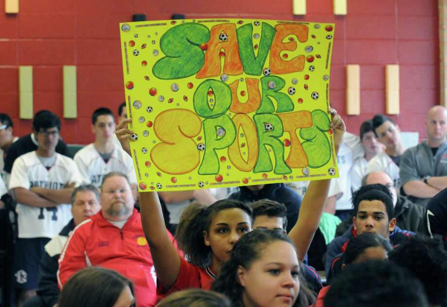 Schenectady High School ninth grade student and softball player Alexia Savignano holds up a sign during a Schenectady school board meeting on Saturday April 5, 2014 in Schenectady, N.Y. Schenectady High School students were out in force on Saturday morning to protest the school boardOs proposed elimination of the districtOs sports programs. (Michael P. Farrell/Times Union) Photo: Michael P. Farrell / 00026387A